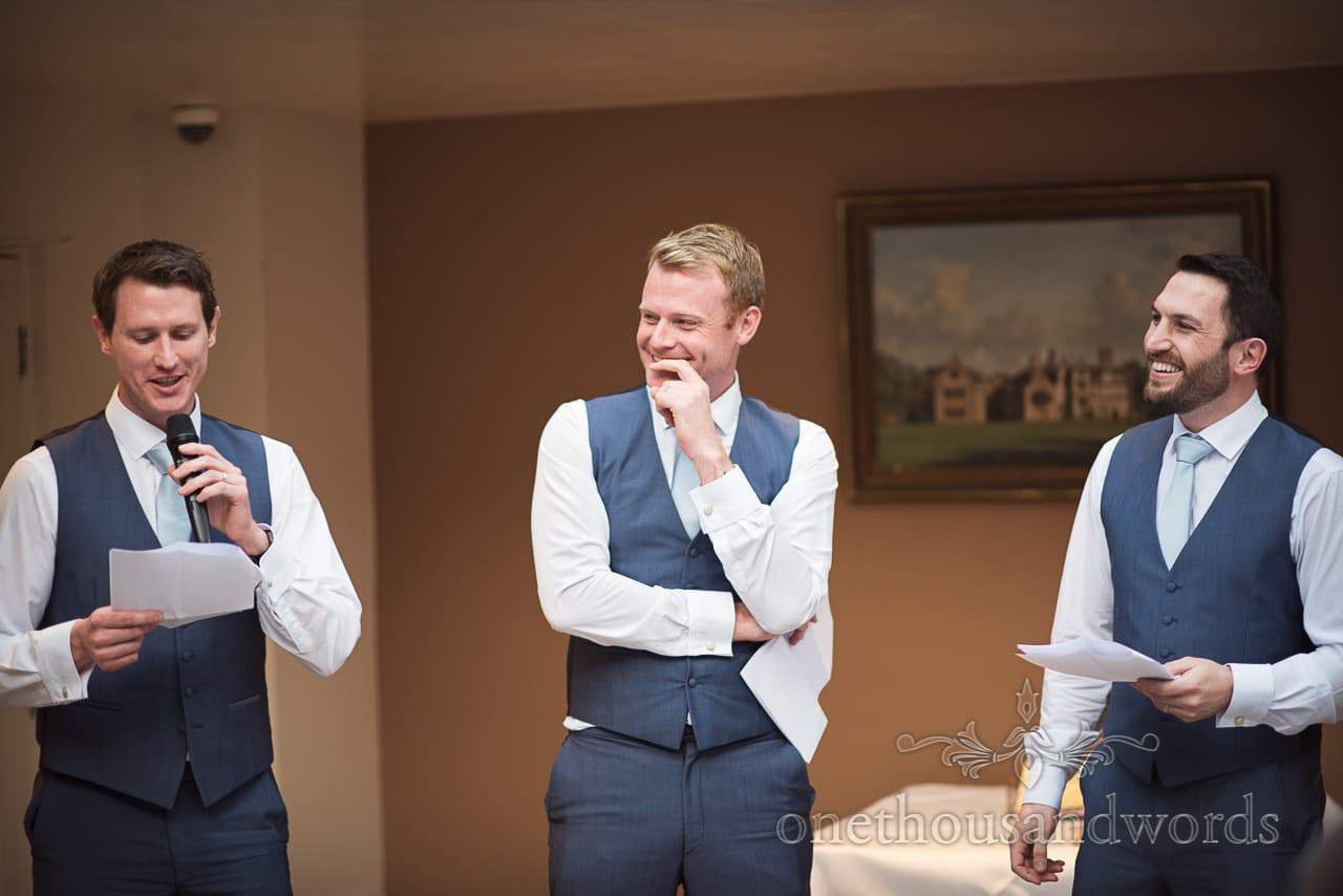 Three best men laugh as they read wedding speeches at Athelhampton House