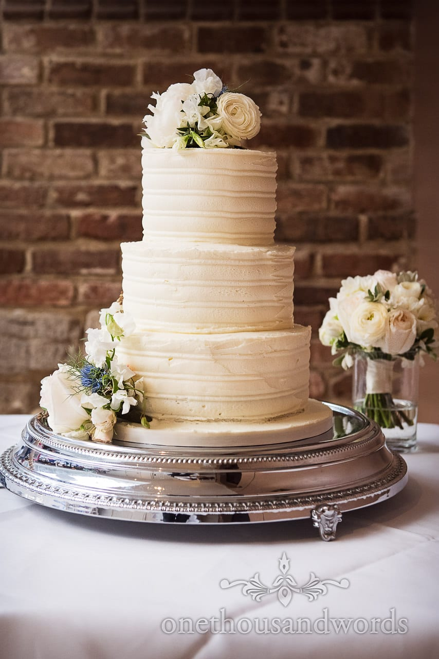 Three tier off white iced wedding cake topped with white flowers against red brick wall
