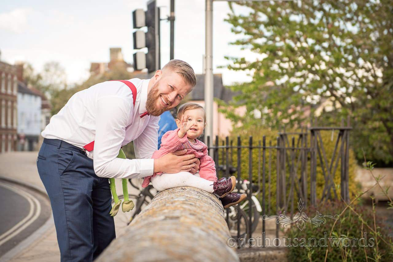 Toddler Wedding Guest On Stone Bridge Waving at Wedding in Christchurch, Dorset by one thousand words wedding photography