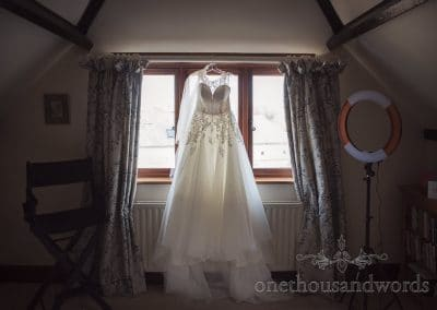Wedding dress with lace detailing hangs glowing in window on wedding morning