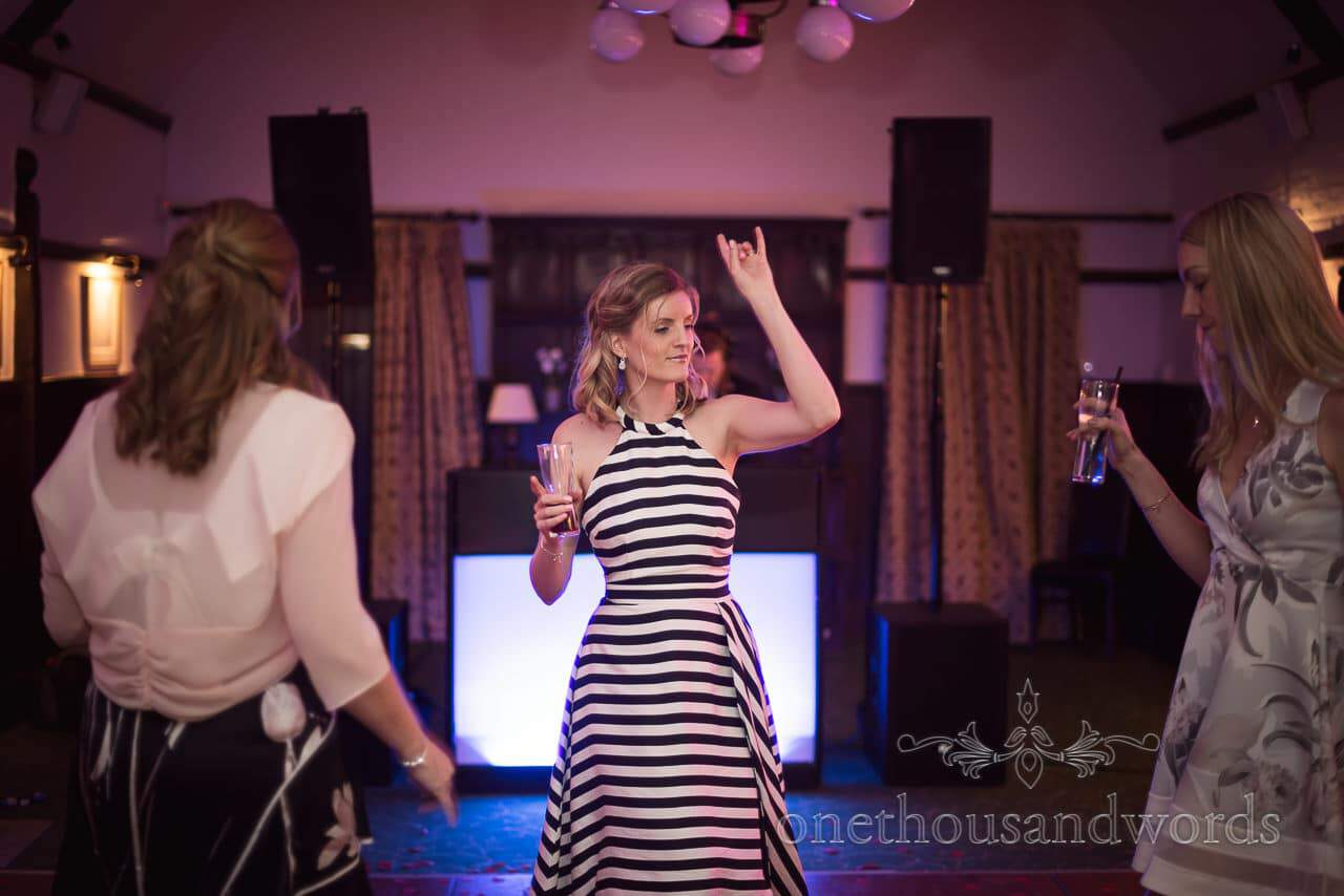 Wedding guest in black and white striped dress dances to wedding DJ