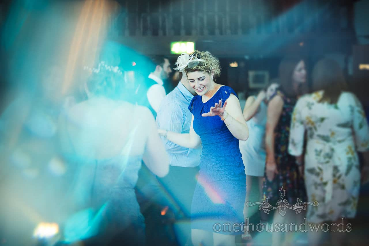 Wedding guest in blue dress dancing under disco lights
