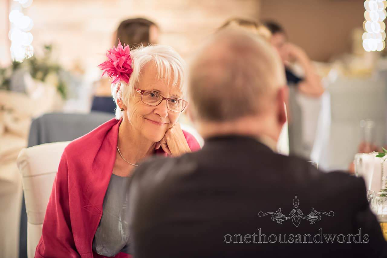 Wedding guest with coordinated pink shawl, glasses and feather head piece listening