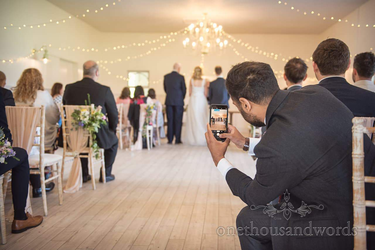 Wedding Guest Take Photograph on Mobile Phone in Aisle During Wedding Ceremony at Kings Arms Pavilion in Christchurch, Dorset