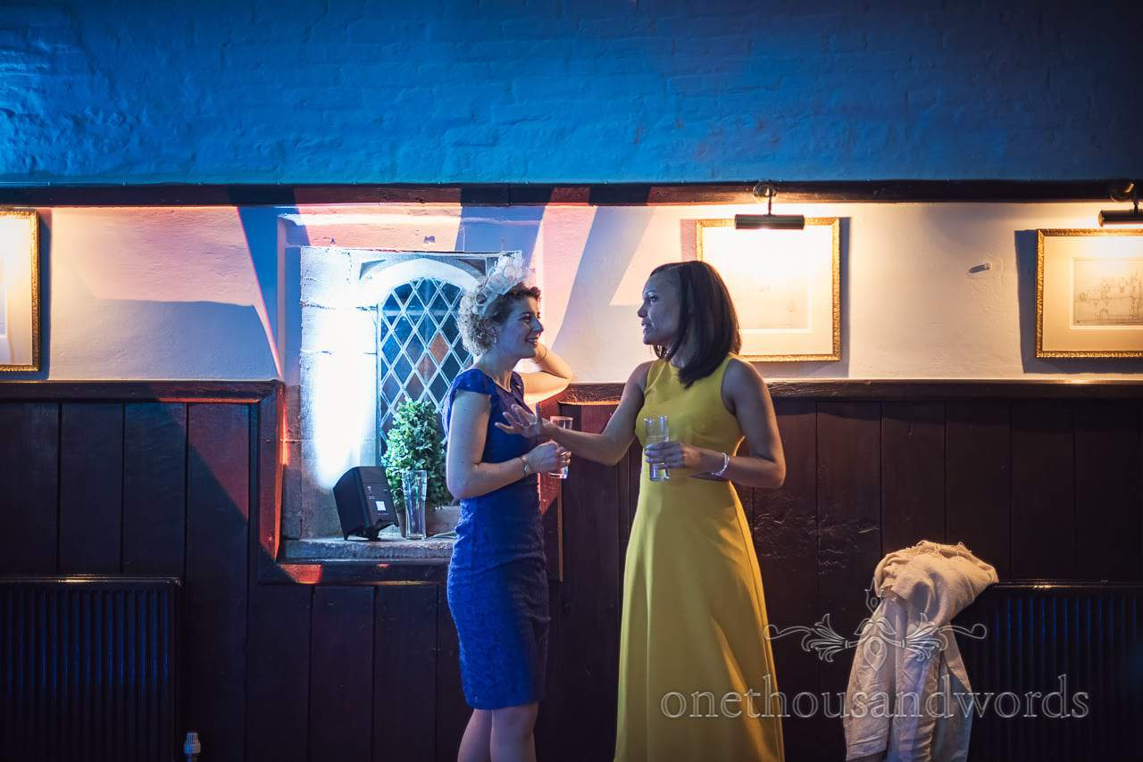 Wedding guests chatting on dance floor under disco lights at Athelhampton House