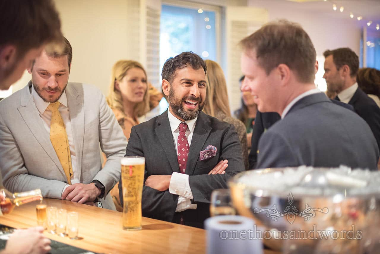 Laughing Wedding Evening Guests Enjoy Beer and Jokes With Groom at Kings Arms Hotel Bar in Dorset