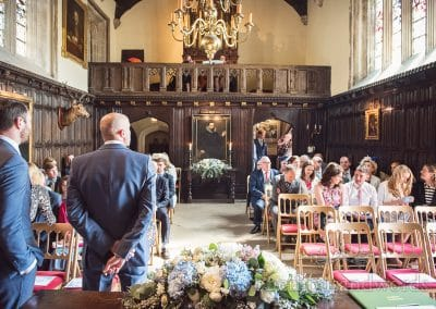 Wedding party await bride at Athelhampton House grand hall