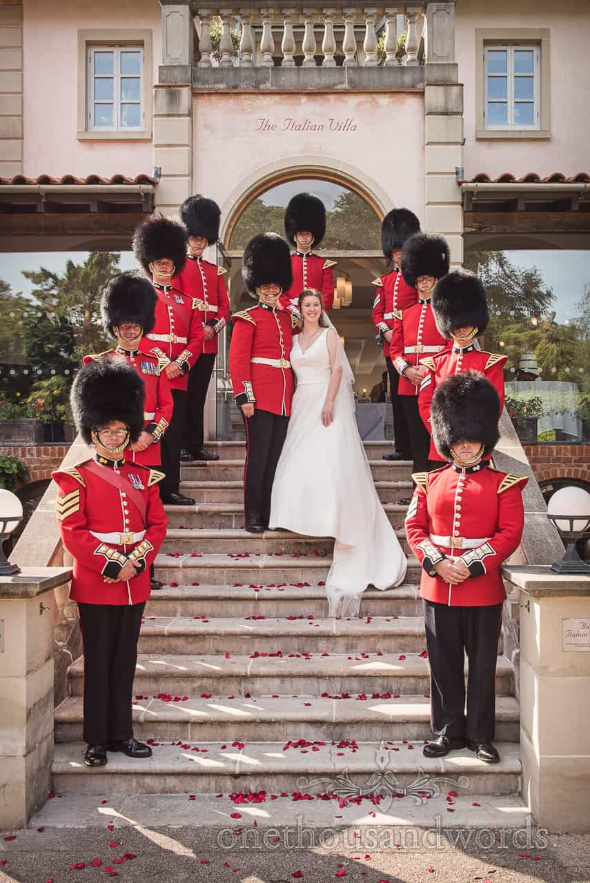 Coldstream Guards in red Military Uniforms and bearskins pose with bride and groom at Italian Villa Poole Wedding venue