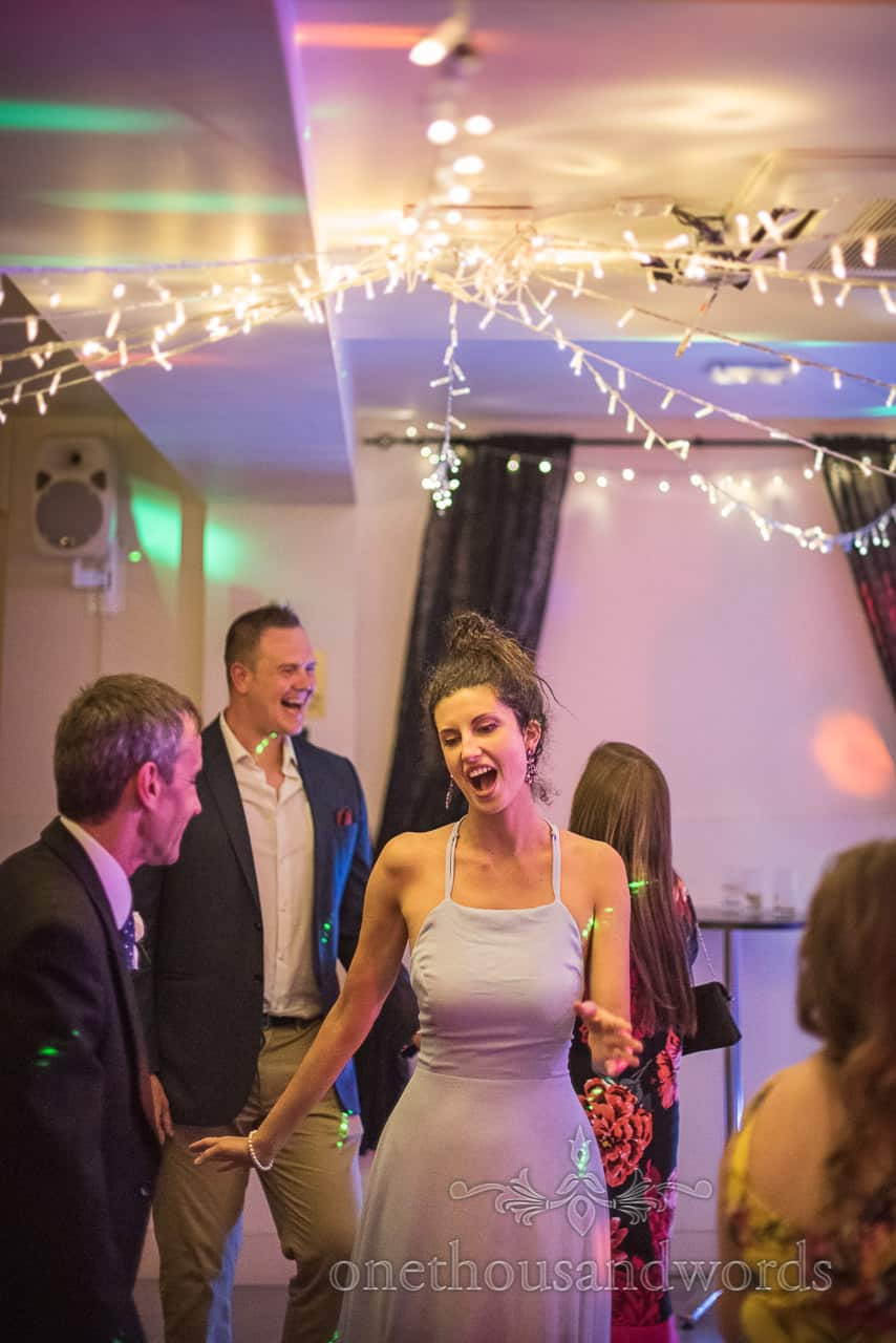Beautiful Wedding Guest wearing Pastel Blue Dress Singing and Dancing at Wedding evening Disco under fairy lights