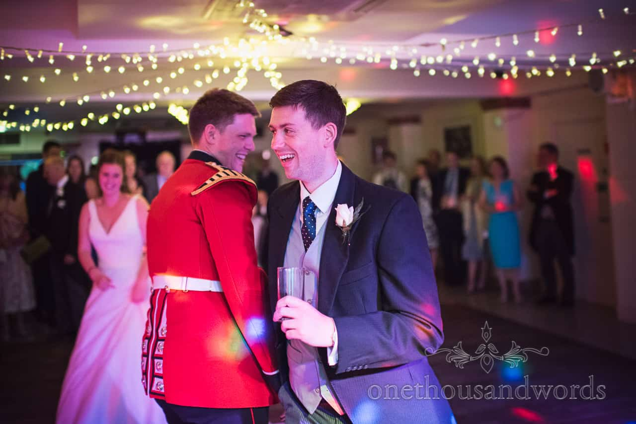 Best Man in morning suit Joins military groom First Dance at wedding disco under coloured lights