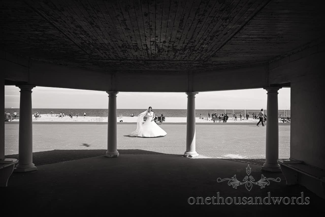 Black and White wedding Photograph of Bride in white wedding dress at Sandbanks Beach in Poole, Dorset