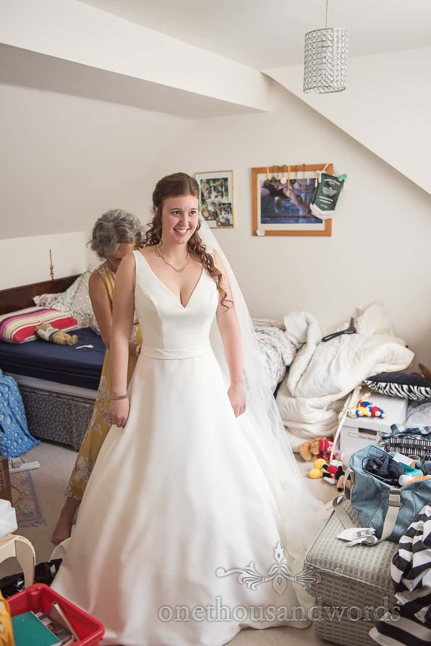 Happy Bride is Buttoned Into white Wedding Dress by Mother of bride on wedding morning Photograph