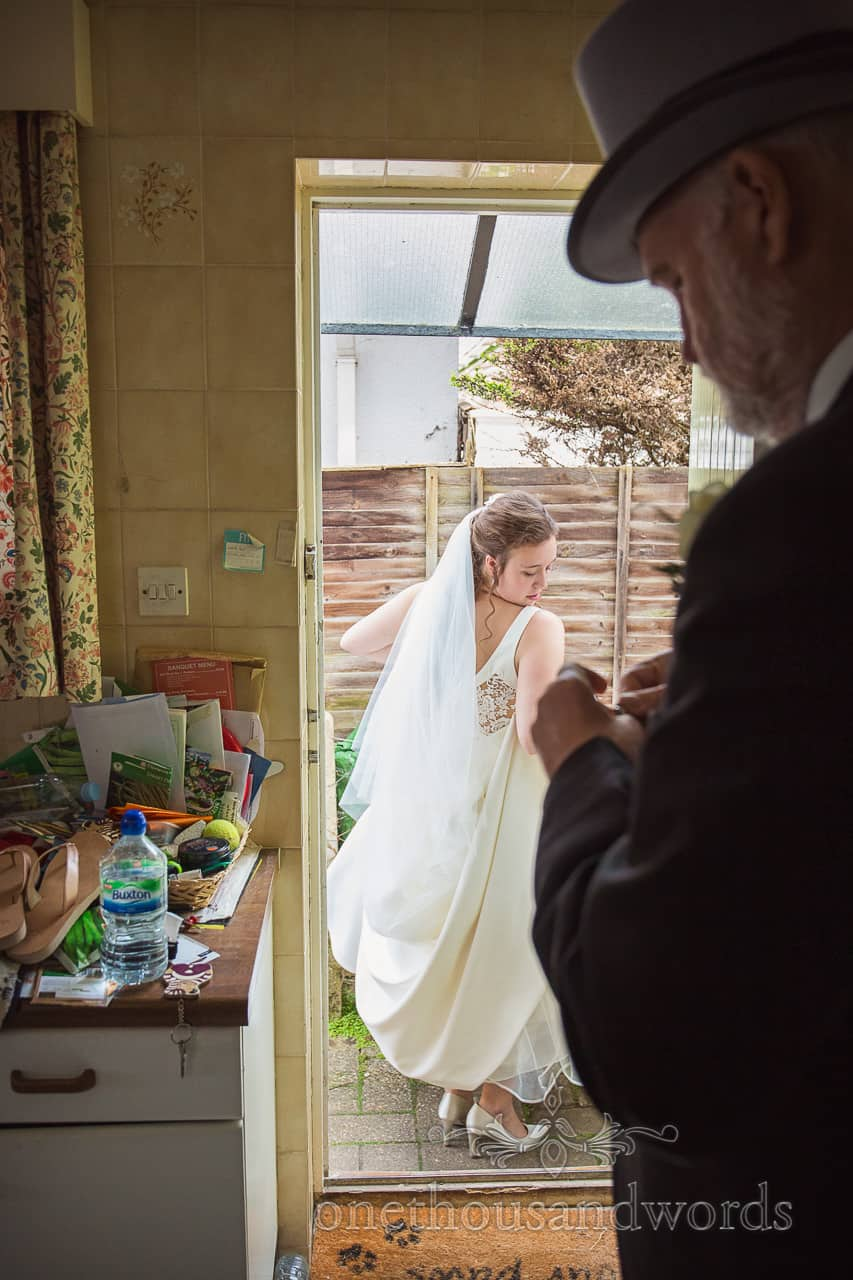 Bride Exits Family Home on wedding morning in White Wedding Dress watched by Father in mornign suit and top hat