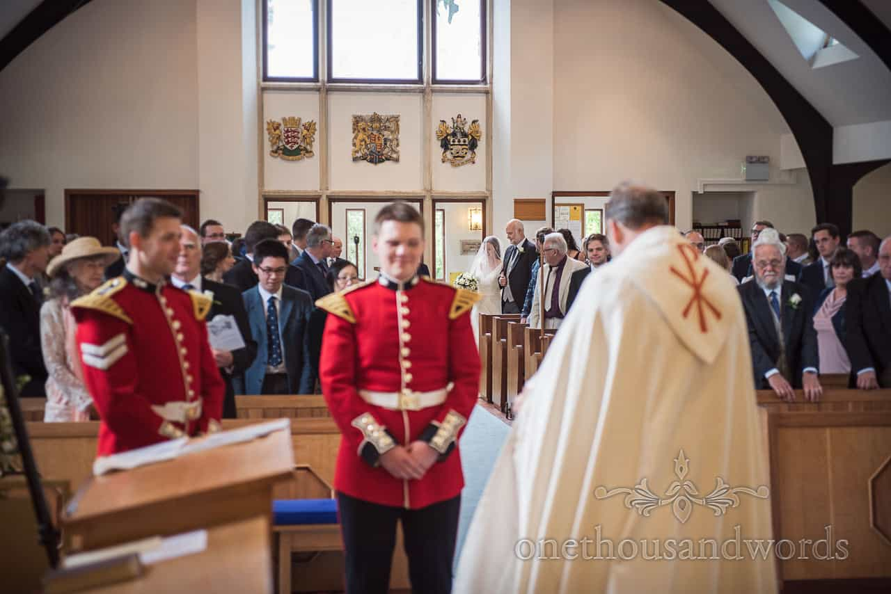 Bride and Father of the bride enter Military Church Wedding Ceremony as groom in red uniform waits at top of aisle