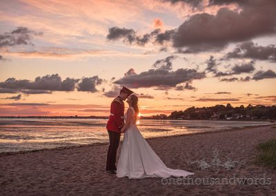 Bride and military Groom on Beach at Wedding with Sunset over sea Kiss in Poole harbour Dorset wedding Photograph