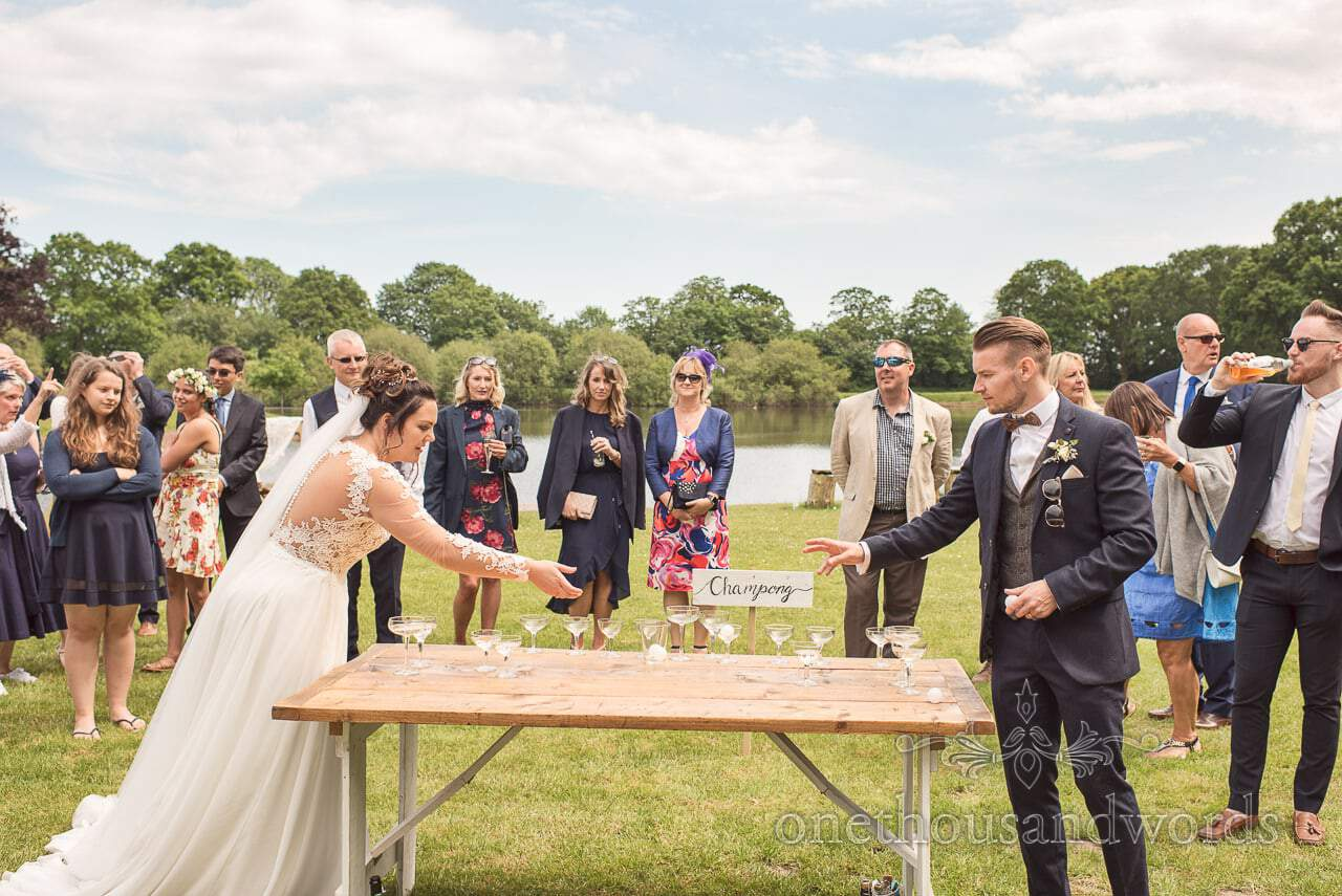 Bride and Groom play Wedding Champong at Sopley Lake Wedding Drinks Reception Documentary Photography by one thousand words