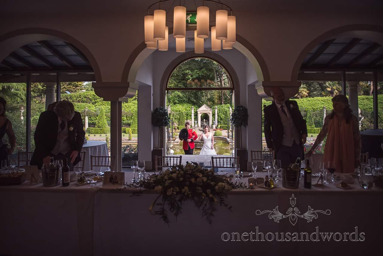 Bride and military Groom in uniform Enter Italian Villa Poole Wedding Breakfast from Italian gardens arm in arm