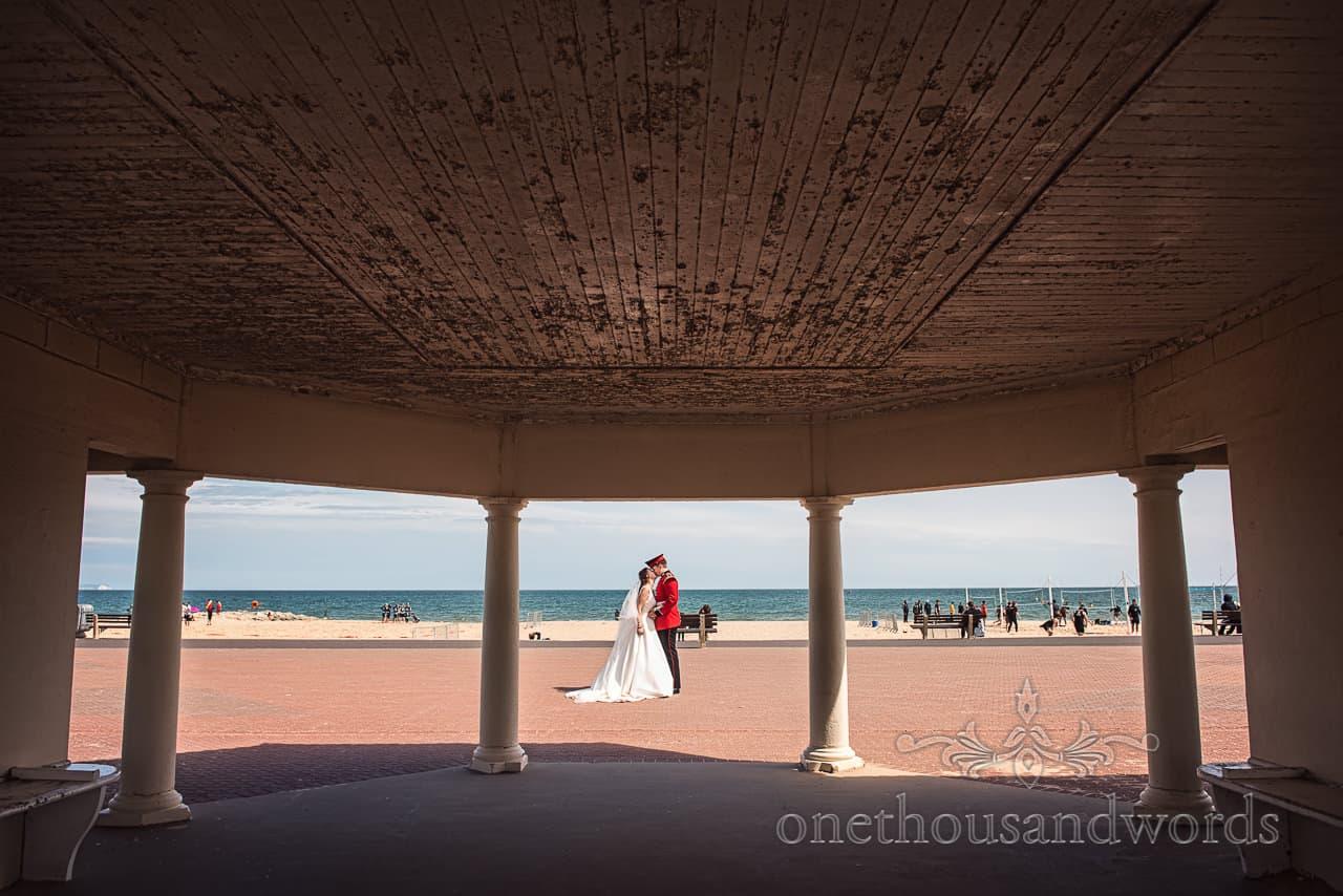 Bride and Groom framed in pavilion columns kissing at Sandbanks Beach Poole Dorset Wedding Photograph