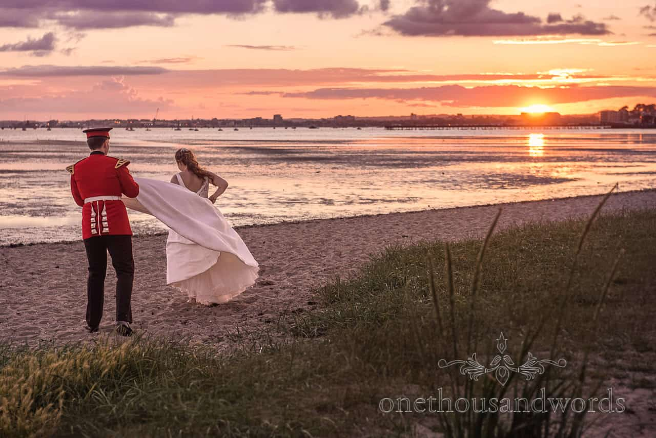 Bride in white wedding dress and Military Groom in uniform take a Beach Sunset Walk wedding Photograph in Poole