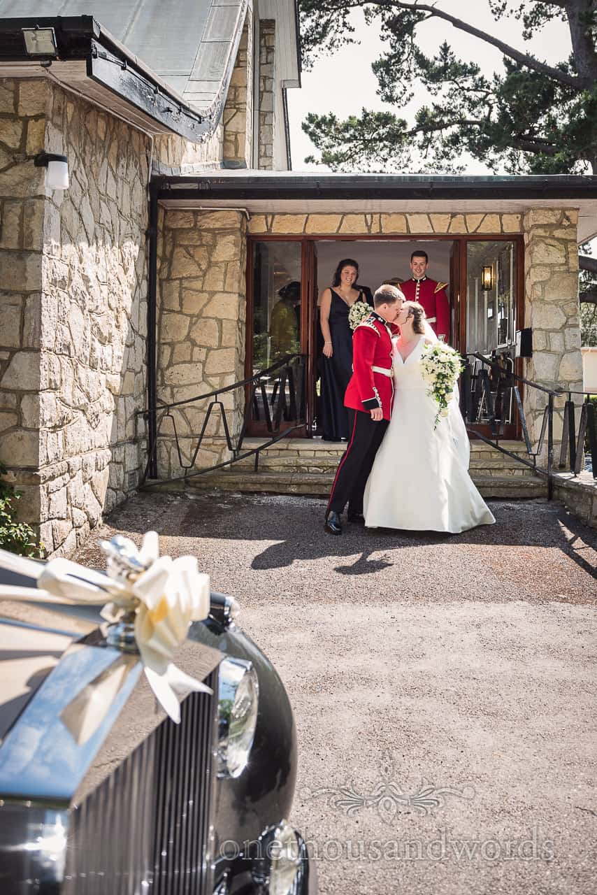 Bride and Military Groom Kiss Outside Church Of The Transfiguration Sandbanks with classic wedding car and ribbons