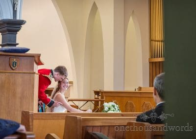 Documentary photograph of Happy Bride and Military Groom in red uniform Sign Marriage Register in Sandbanks Poole Church