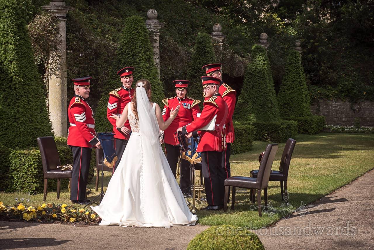 Bride Talks to the Coldstream Guard Band in red military uniforms in the Italian gardens at The Italian Villa Poole Wedding Venue