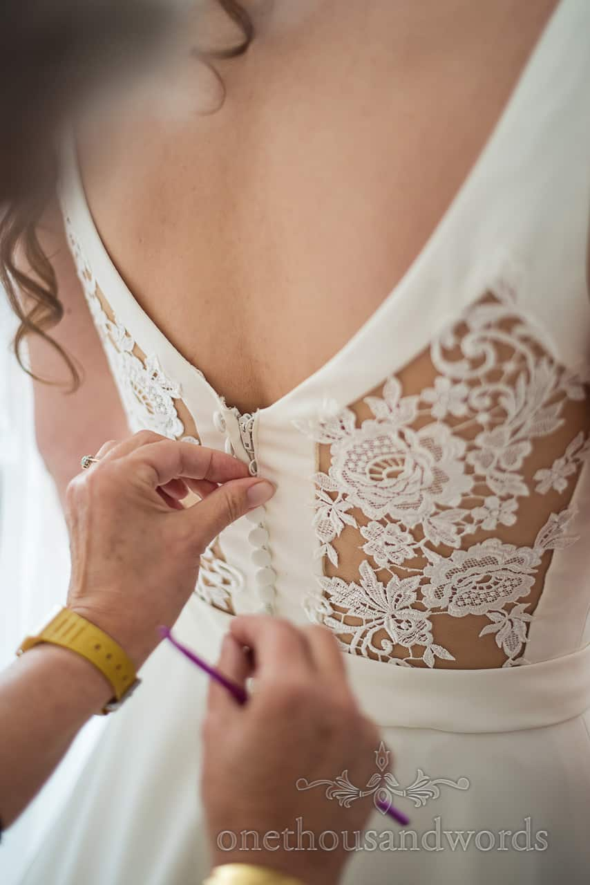 Close up photograph of Bride being buttoned into wedding dress with lace detail panels by mother using a crochet hook