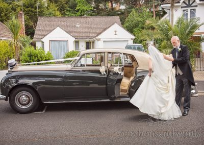 Bride in White wedding Dress helped into Classic Wedding Car with top hat on badge by father in morning suit in Poole