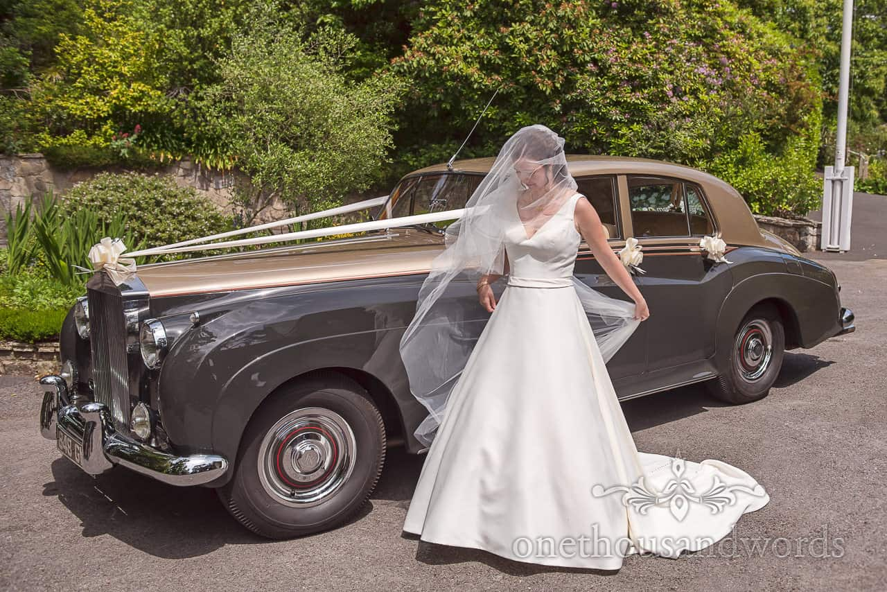 Bride in White wedding Dress adjusts her Veil with Classic Green and gold Wedding Car outside church wedding venue