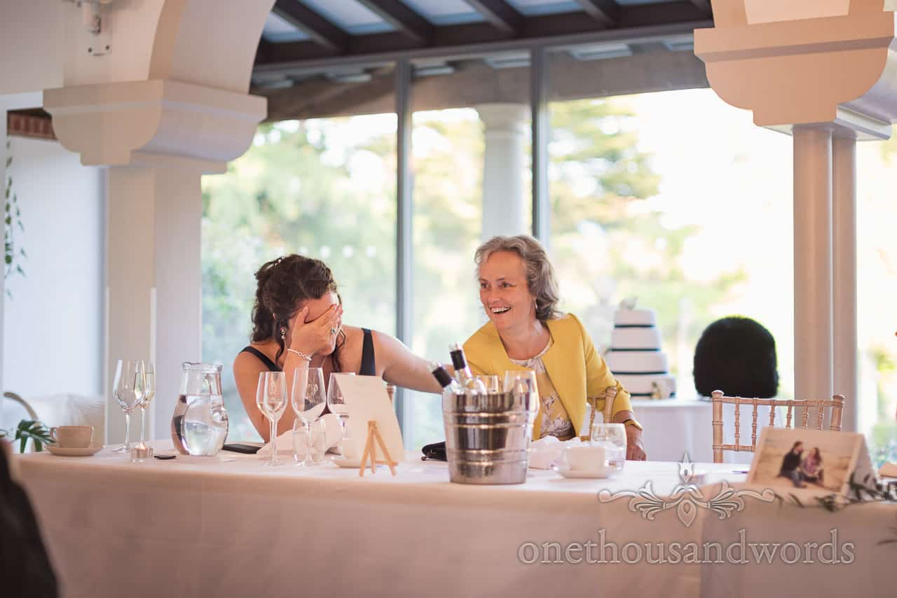 Brides Sister Holds her Head in Hand whilst laughing at Wedding Speeches at top table at The Italian Villa Poole wedding venue