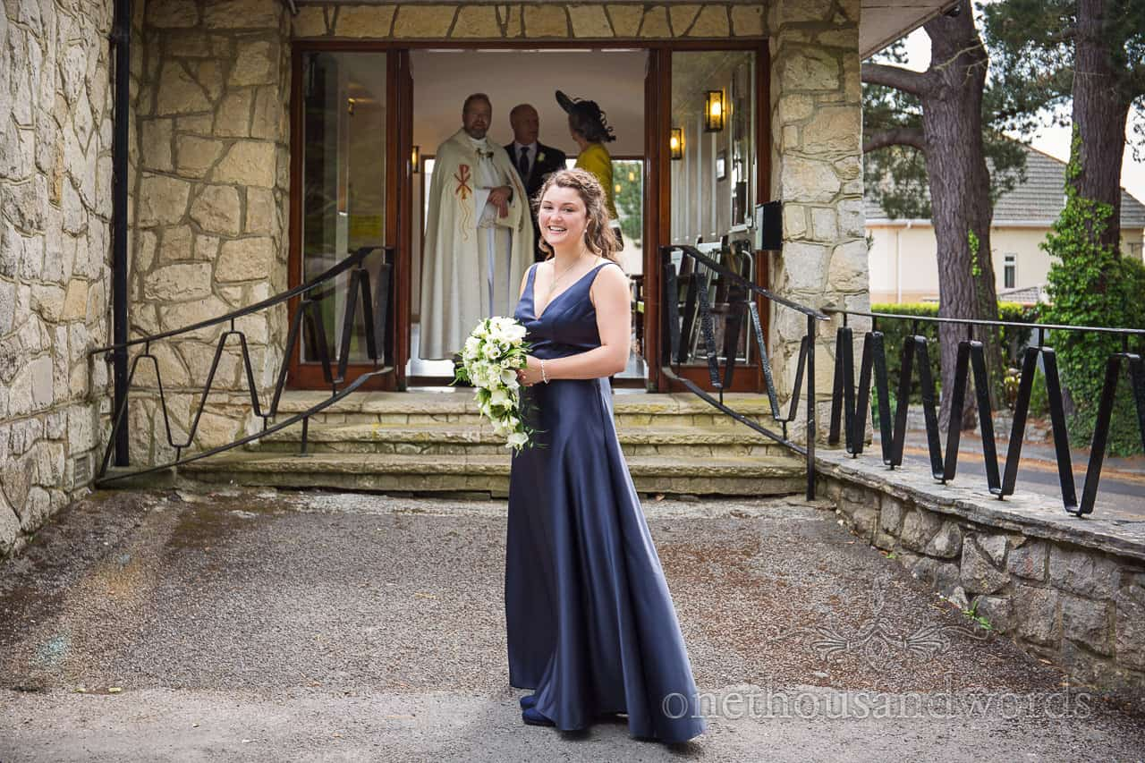 Bridesmaid in Navy Blue bridesmaids Dress with white wedding flowers Outside Our Lady of Transfiguration church in Sandbanks