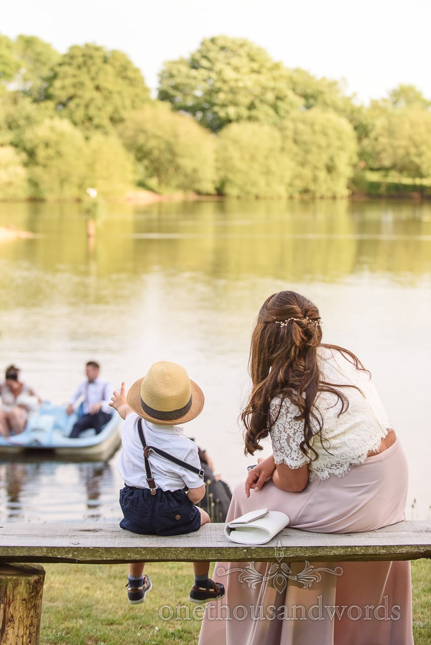 Bridesmaid and Page Boy Watch Bride Groom in Pedalo at Sopley Lake Wedding photo by one thousand words wedding photographers