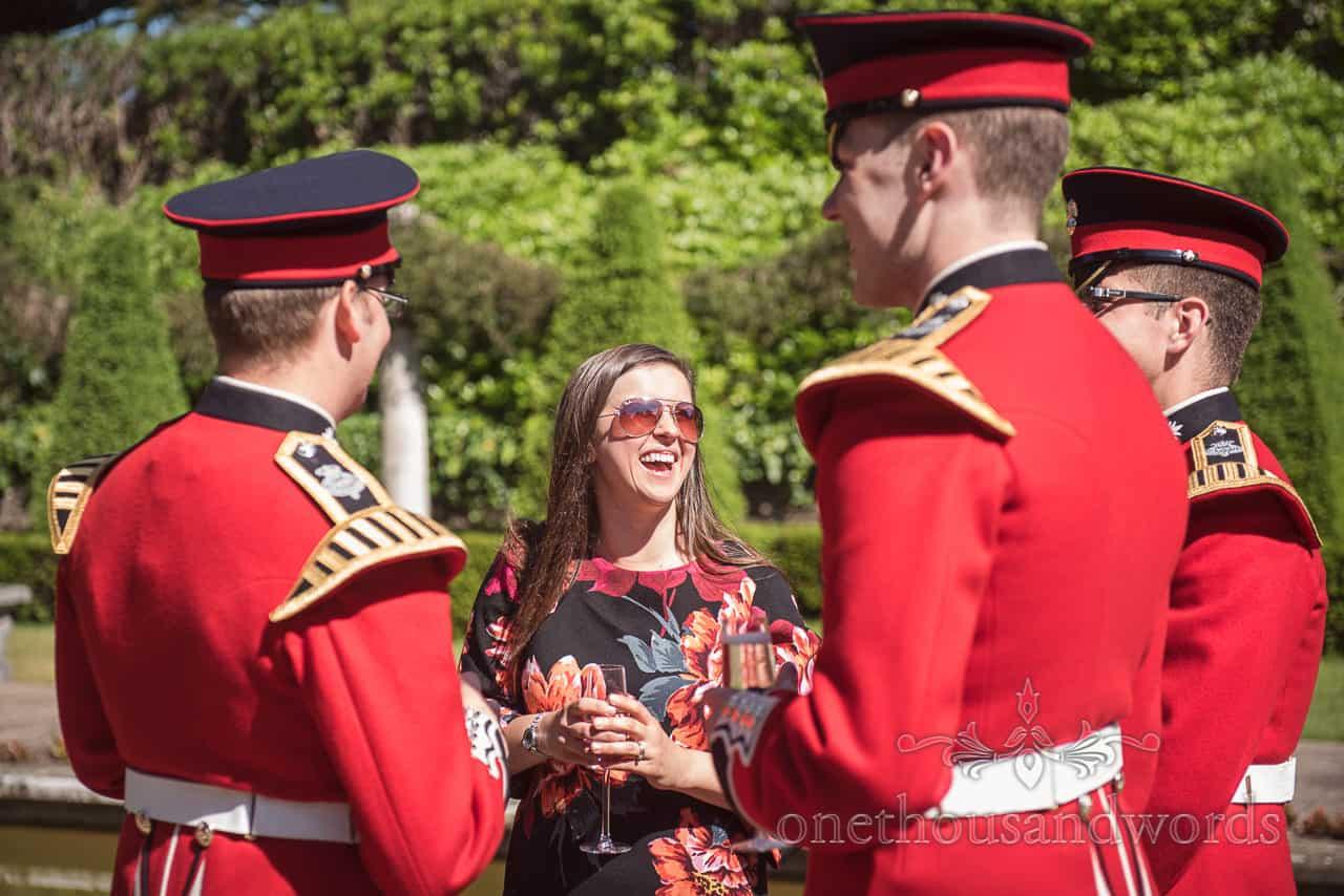 Coldstream Guards in Red Uniforms make female Wedding Guest laugh at Italian Villa wedding drinks reception in summer sun