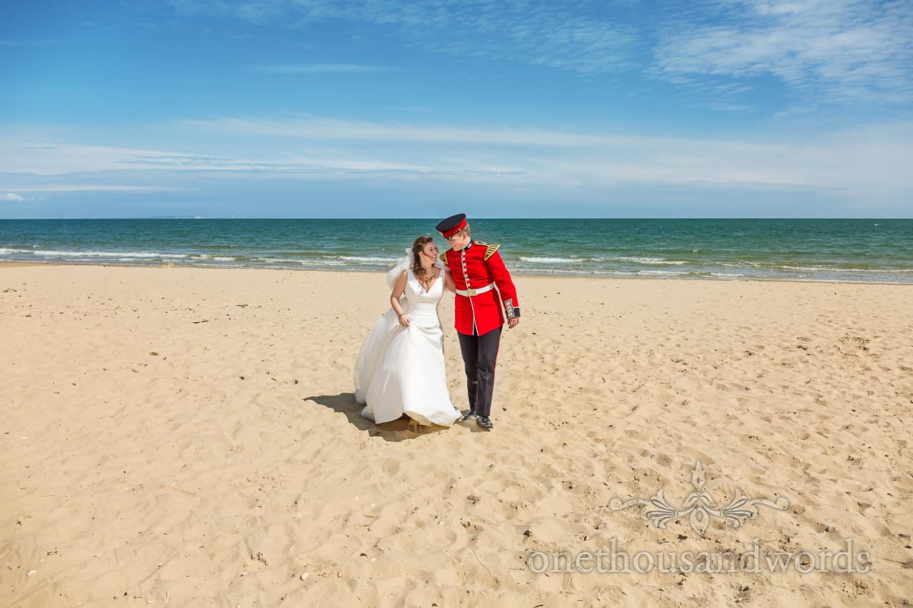 Photograph of Dorset Beach with Wedding Couple. Bride wears white wedding dress groom in red military uniform in summer sun