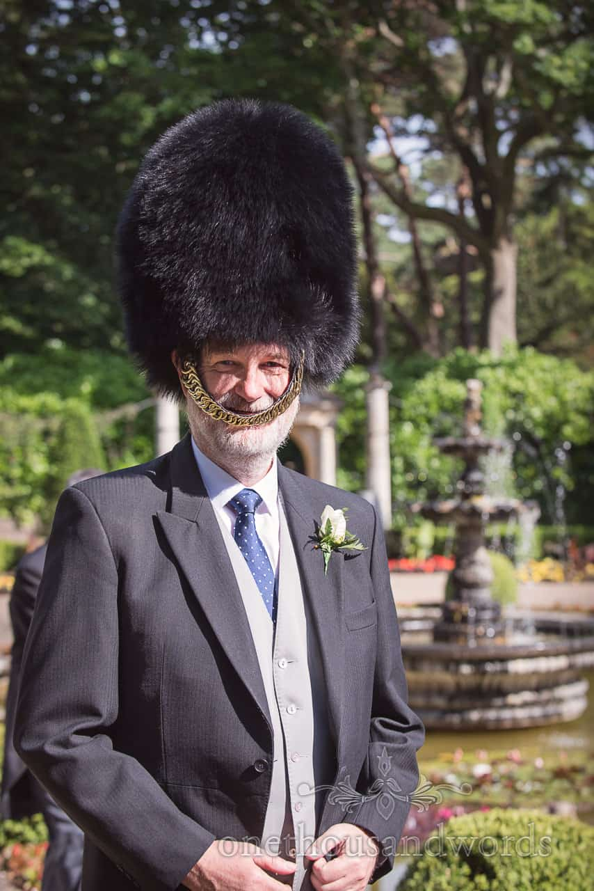 Father of Bride in morning suit wears Military Bearskin Hat at Italian Villa Wedding drinks reception in the gardens