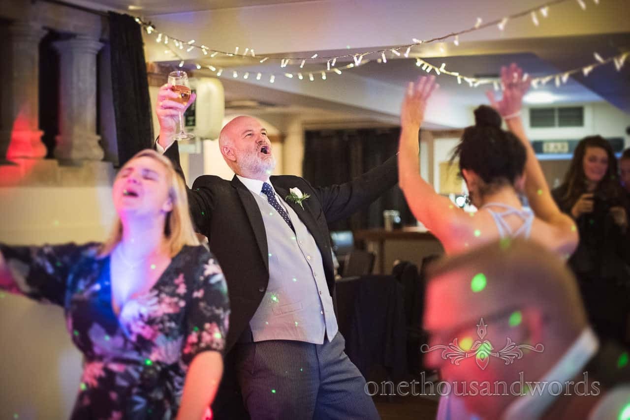Father of the Bride in morning suit Singing and Dancing with wedding guests at Wedding Evening Disco Photograph