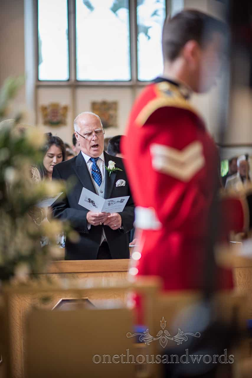 Father of the Groom in morning suit expressively Singing at Military Church Wedding Ceremony