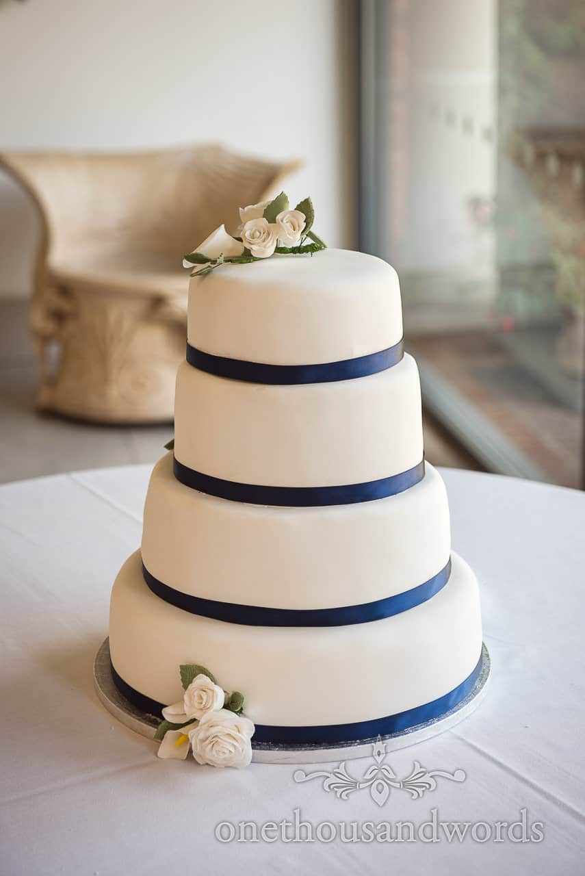 Simple but beautiful Four Tier White white Wedding Cake with navy Blue Ribbon and white flowers made from icing