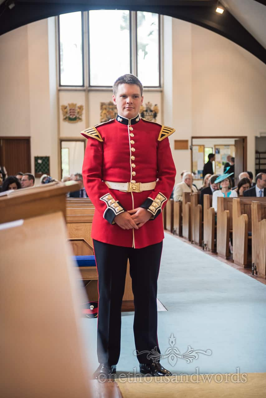 Groom in red Military Uniform Waits patiently at top of aisle for bride at Church wedding Ceremony in Dorset
