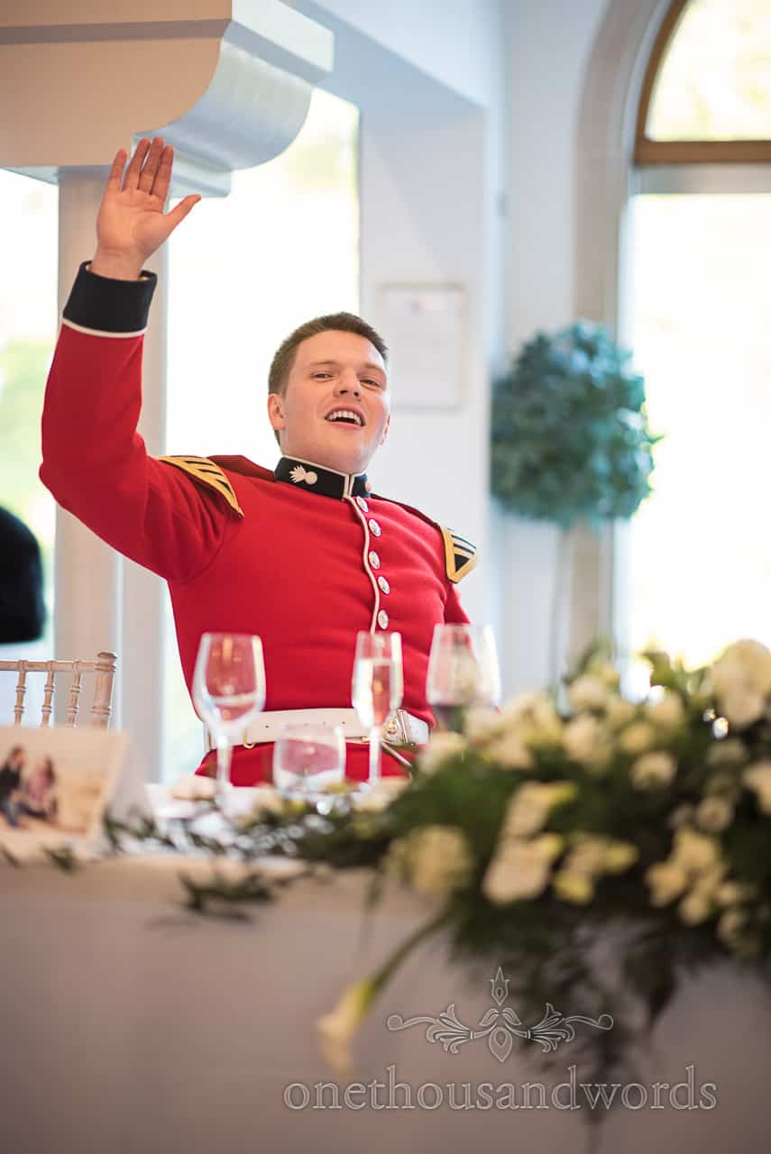 Happy smiling groom in Red Military Uniform at top table raises his hand to object to Wedding Speeches