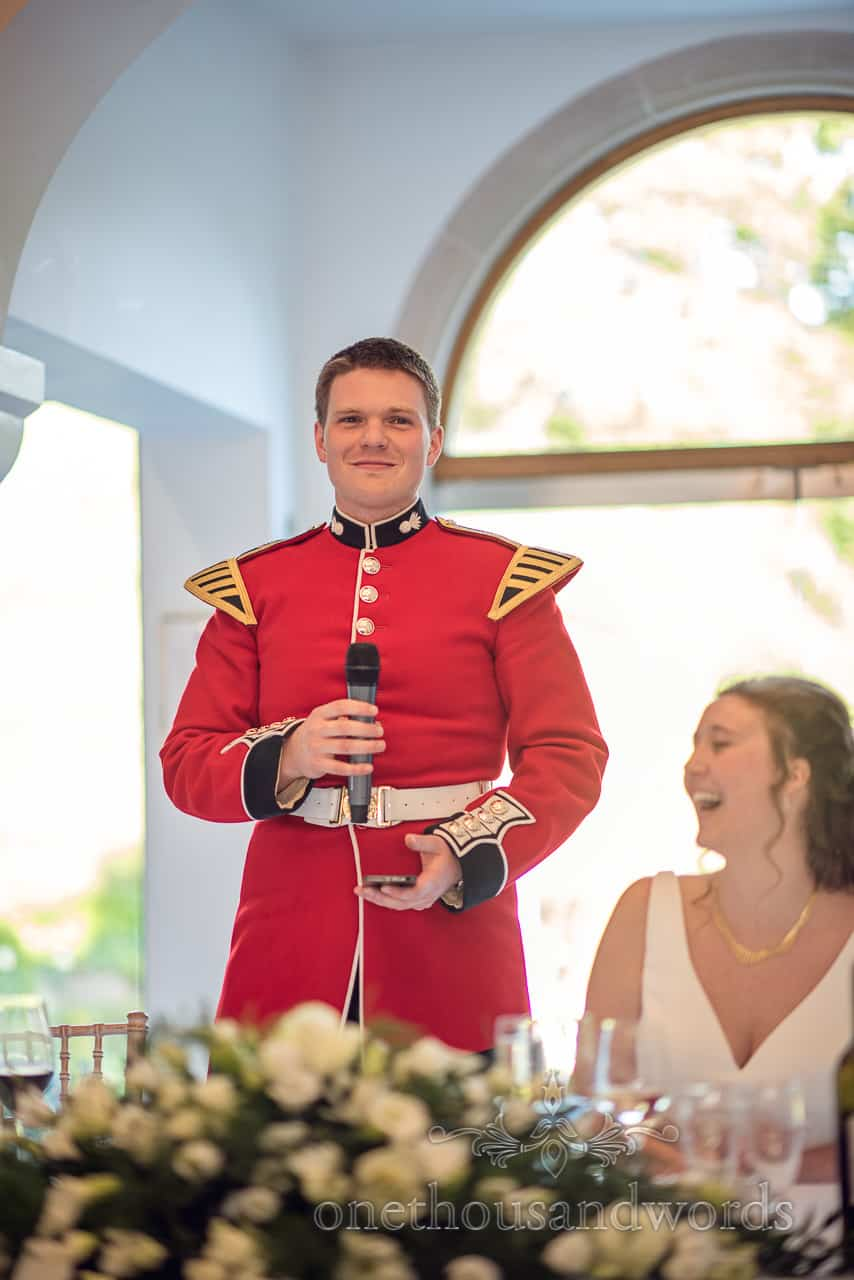 Groom in Red Military Uniform Makes Wedding Speech using a Microphone and mobile phone