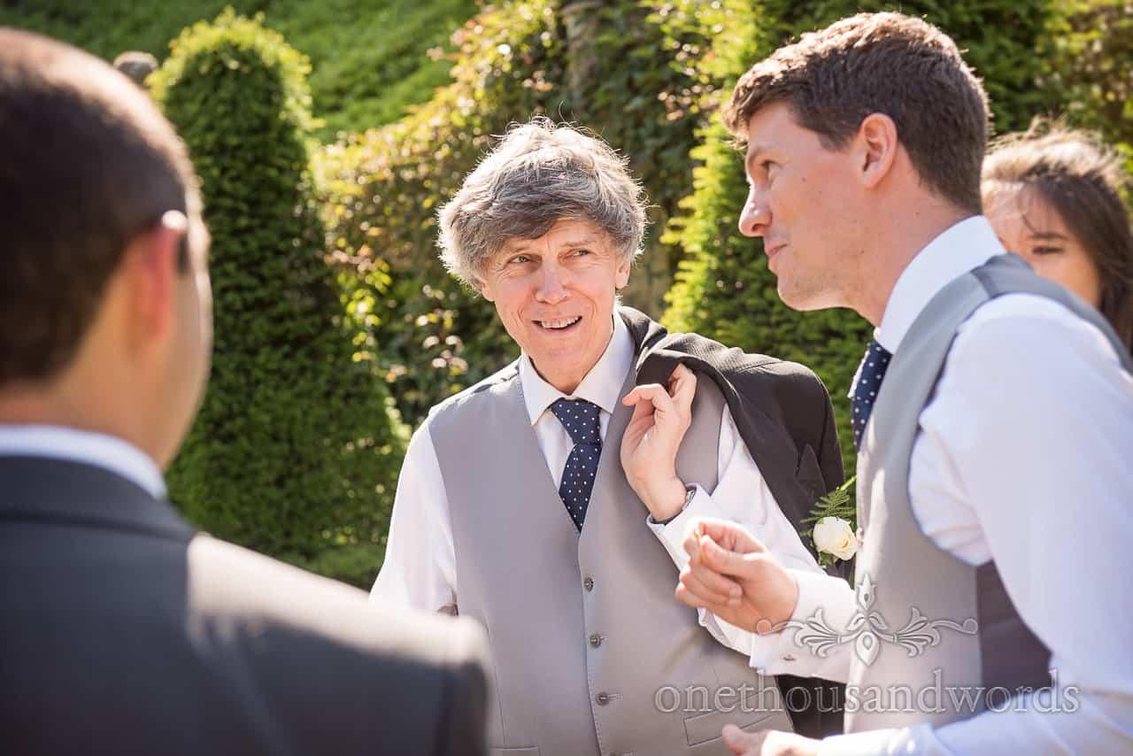 Portrait photograph of Groomsman in Grey Waistcoat in the sunshine smiling at Italian Villa Wedding Drinks Reception