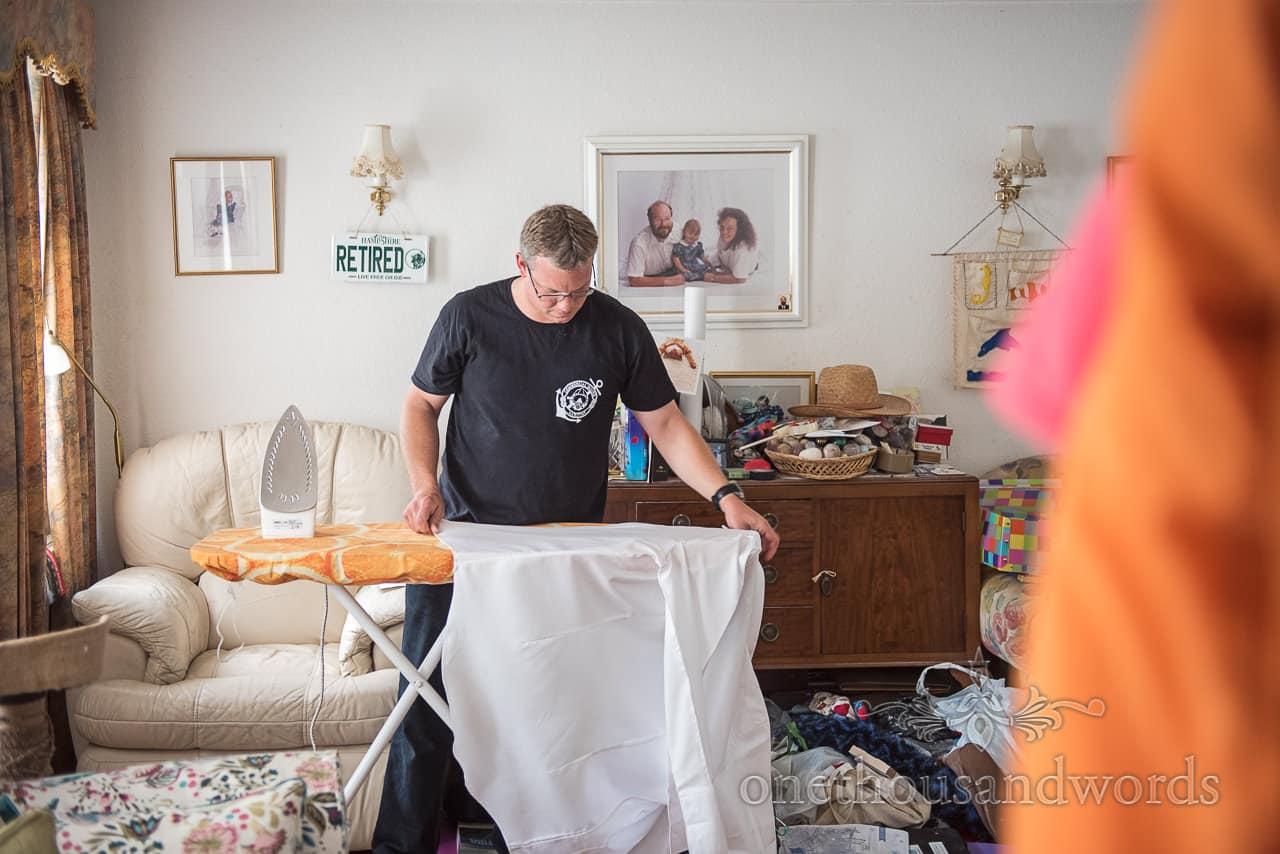Groomsman Irons white Wedding Shirt at family home during wedding Morning documentary Photographs