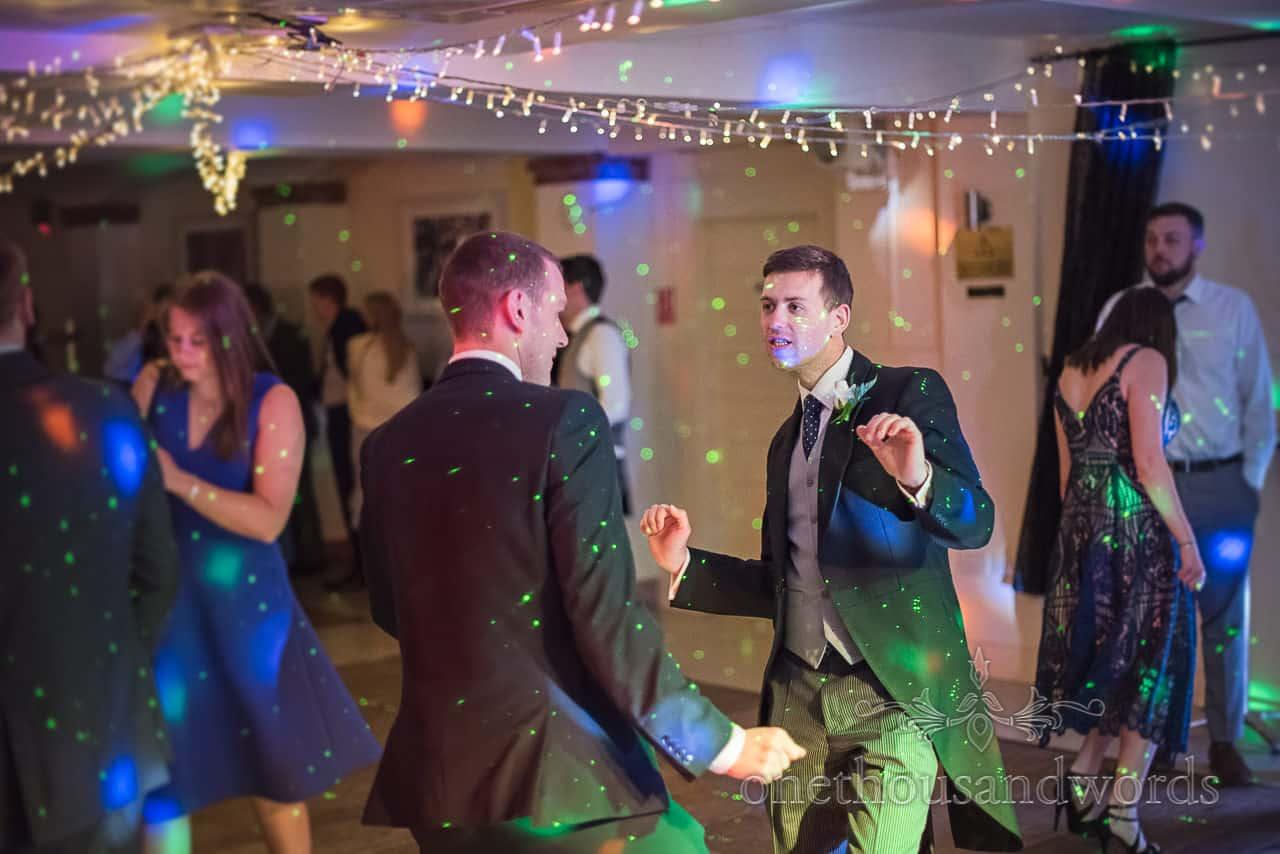 Groomsmen in black and grey Morning Suits dancing on Italian Villa Dance Floor under fairy lights with green lasers