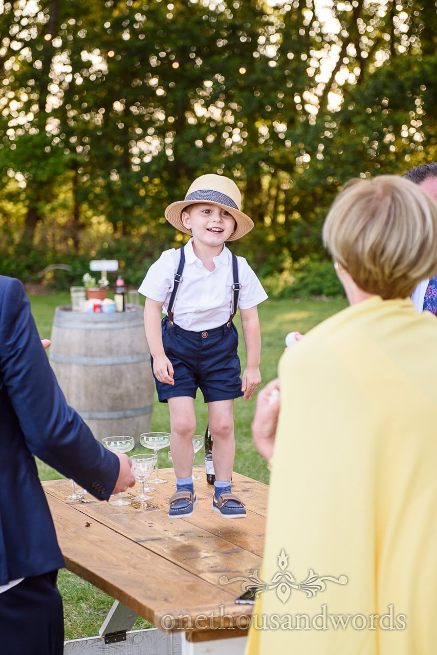 Hovering Mid Jump Excited Page Boy in Braces and Straw Hat at Sopley Lake wedding photographs by one thousand words photography