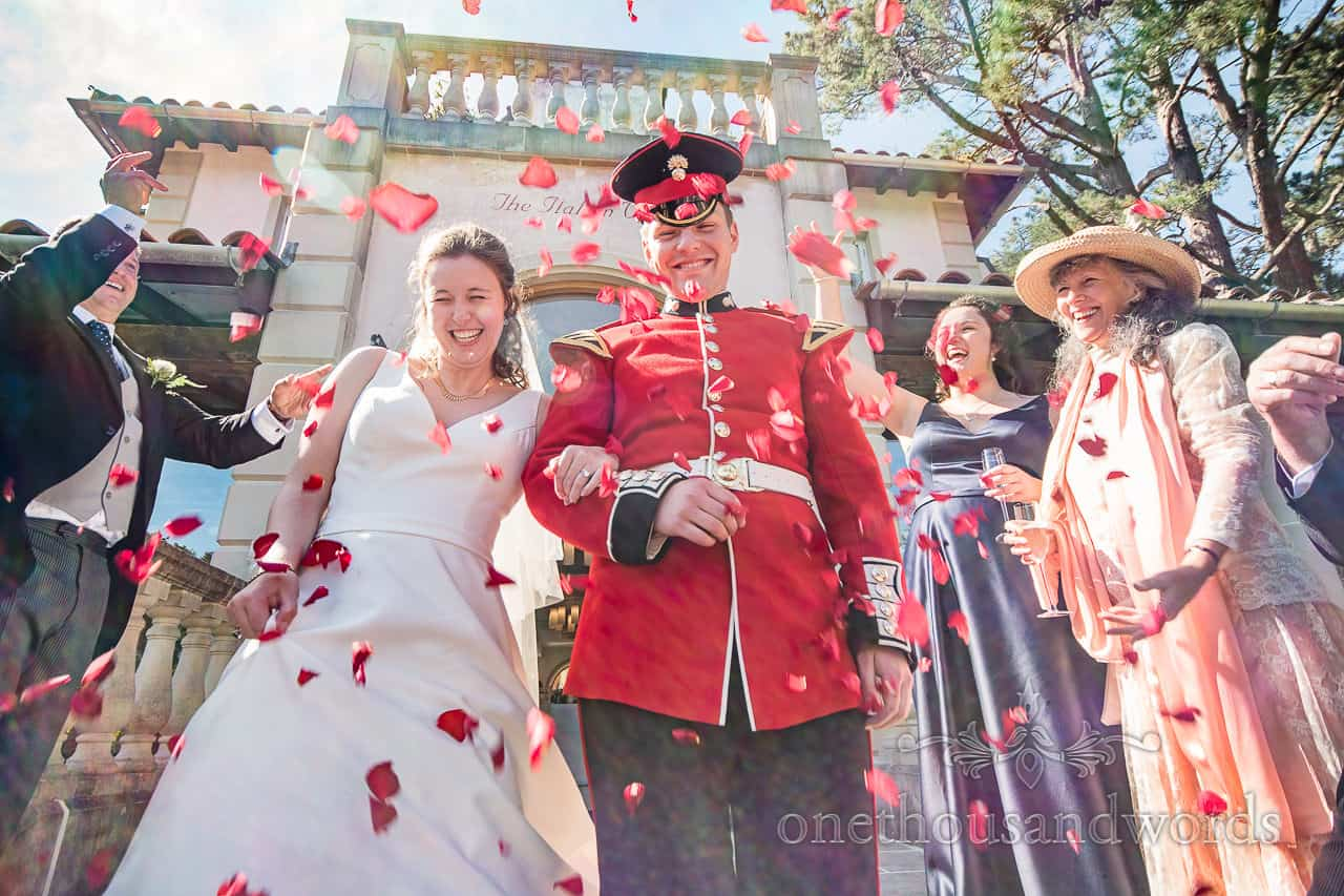 Italian Villa Poole Wedding Confetti Photograph with military groom in red uniform and red confetti documentary wedding photograph