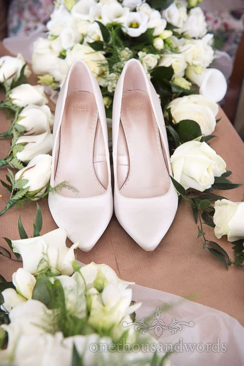 Simple Ivory Silk Wedding Shoes amongst White Wedding Flowers with green foliage detail photograph