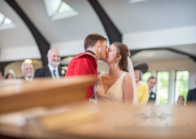 Military Groom in red uniform and Bride in white wedding dress have First Kiss during Church Wedding Ceremony in Dorset