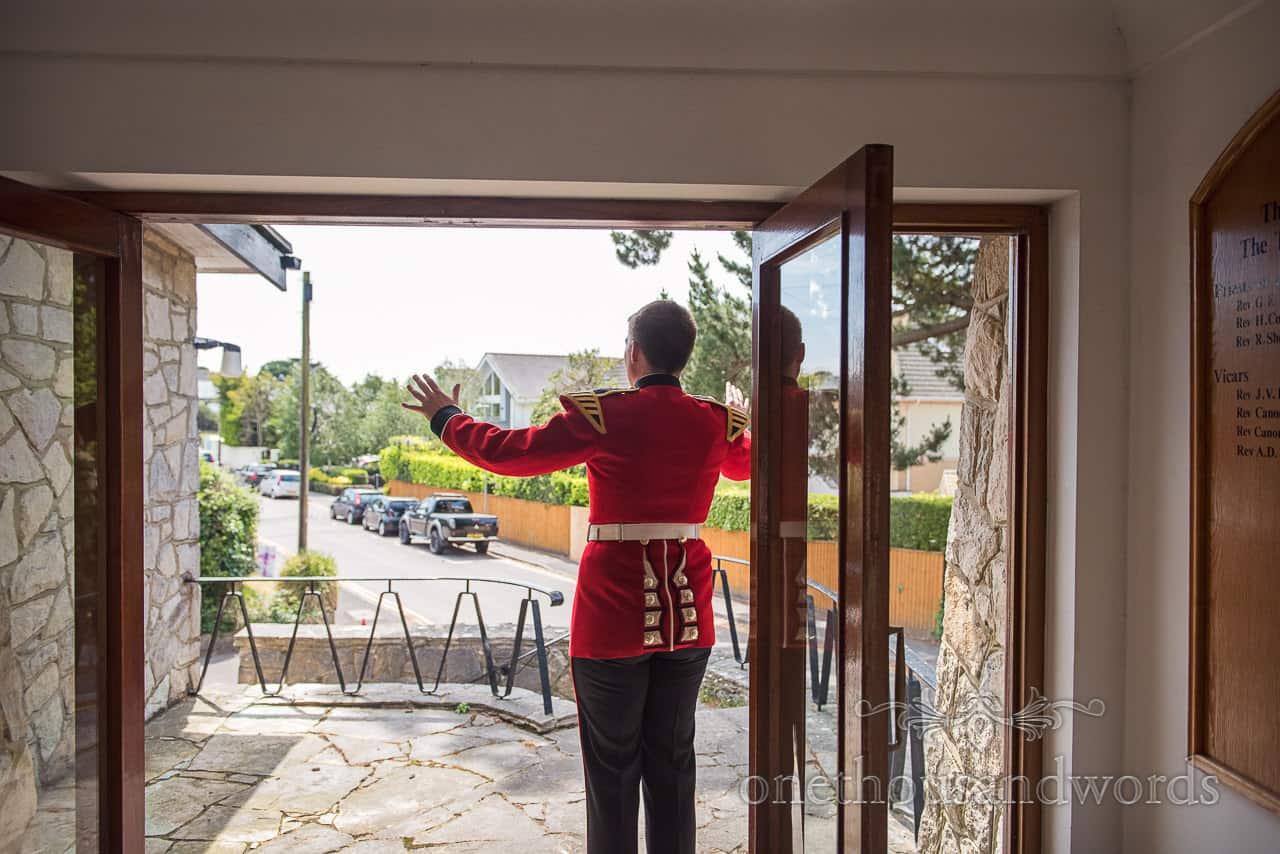 Military Groom in red uniform waving arms stood in Church Doorway on Wedding Morning in Dorset