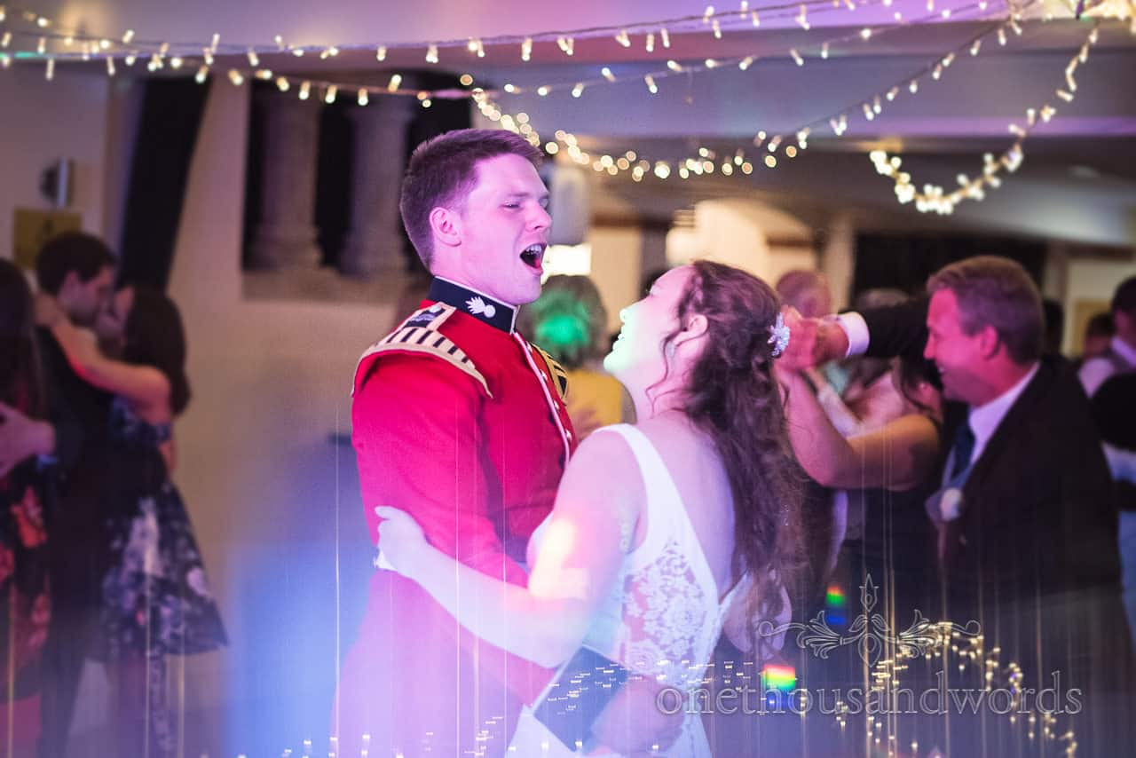 Military Groom in red uniform Sings during First Dance under disco and fairy lights at Italian Villa Poole Wedding